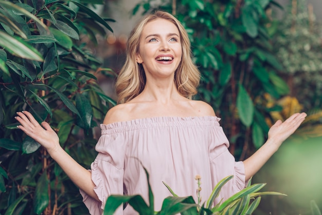 Carefree blonde happy young woman standing near the plants shrugging her hands