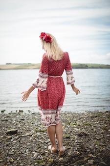 Carefree blonde woman wearing a flower tiara standing near a river