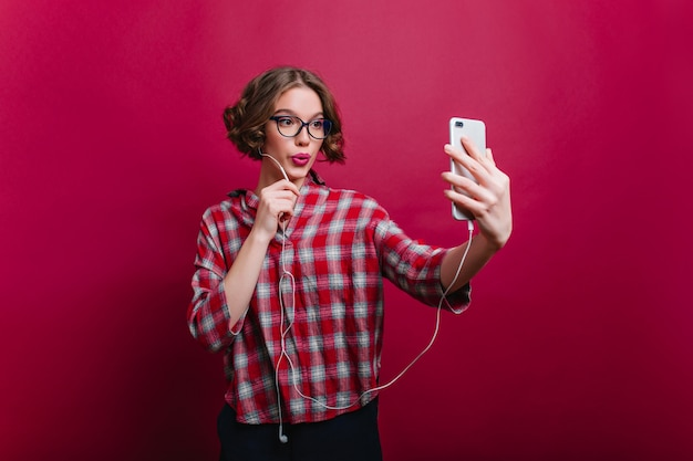 気楽な茶色の髪の女の子がチェックのカジュアルシャツを着て自分撮りをしているメガネをかけた陽気な若い女性がキスの表情でポーズをとって電話を使っている屋内写真。