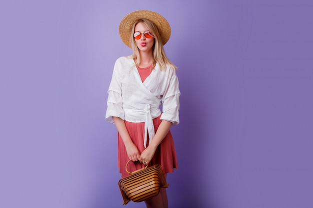 Carefree brunette woman in trendy pink dress and straw hat holding bamboo bag on violet.