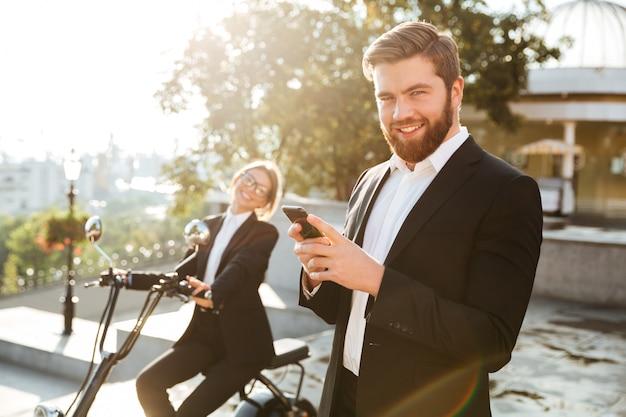 Uomo spensierato di affari che posa all'aperto facendo uso del telefono