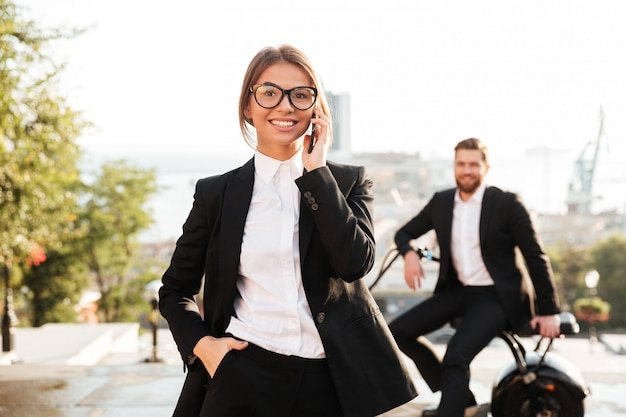Carefree business woman posing outdoors and talking by phone