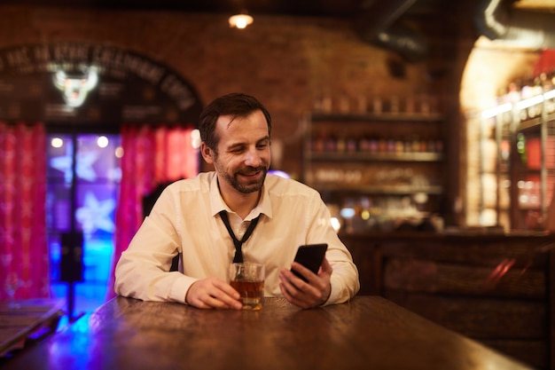 Carefree businessman drinking in bar