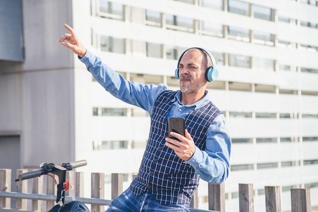 Беззаботный бизнесмен с наушниками, счастливо слушающий музыку