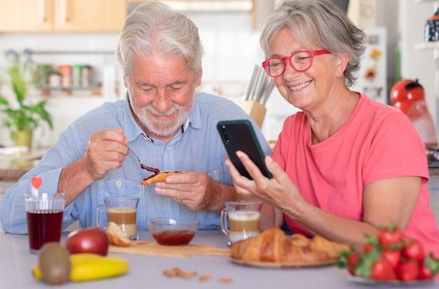 Беззаботная кавказская пара завтракает дома. жена с помощью мобильного телефона. пожилые люди расслаблены и счастливы, наслаждаясь едой и напитками