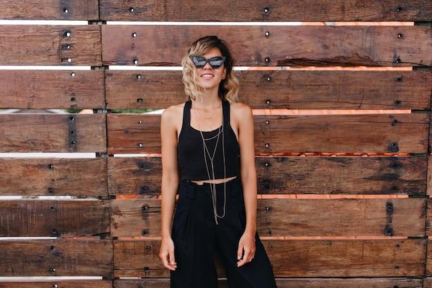 木製の壁の近くに立っている黒い服を着たのんきな白人女性モデル。写真撮影を楽しんでいるブロンドの髪を持つリラックスした若い女性。