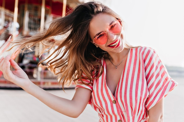 Carefree caucasian lady playing with her hair near carousel. excited beautiful girl expressing good emotions in amusement park.