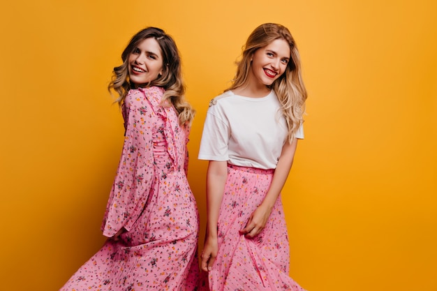 핑크 스커트 포즈에 평온한 백인 여자 미소로 노란색 벽에 서있는 매혹적인 자매.