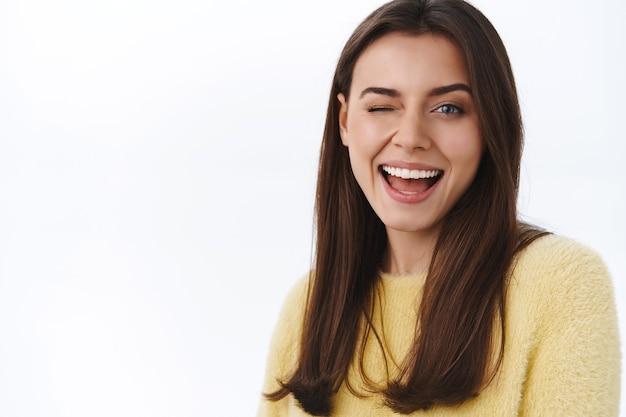 Spensierata sfacciata giovane donna bruna in maglione giallo, strizza l'occhio alla macchina fotografica civettuola e sorridente, assicura tutto alla grande, incoraggia a goderti una fantastica giornata di primavera