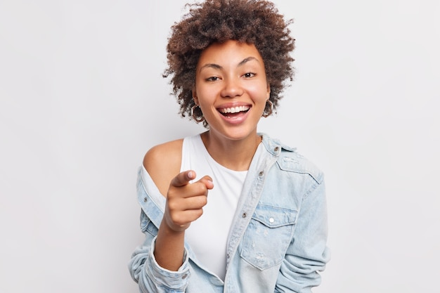 Carefree cheerful afro american woman points at you smiles broadly sees something funny in front dressed in fashionable clothes isolated over white wall