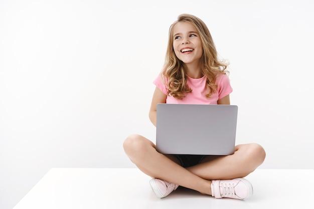 Беззаботный жизнерадостный белокурый кавказский милый ребенок молодая сестра сидит на полу с ноутбуком, радостно смеется, учится онлайн, цифровое образование, отводит взгляд влево copyspace, счастливо улыбается, изучает новый язык