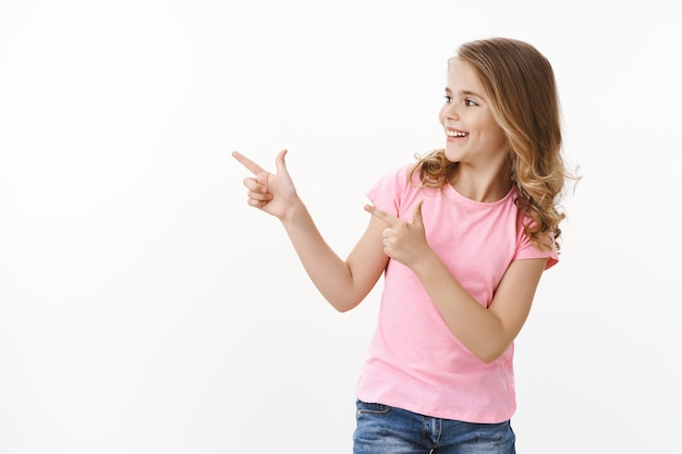 Беззаботная веселая улыбающаяся счастливая белокурая маленькая девочка повернула налево, указывая пальцем на пистолеты, копируя пространство, приветствуя школьных друзей, улыбаясь в восторге. ребенок проверяет крутое промо copyspace, белая стена