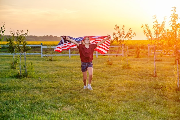 Carefree child running in field with blowing american flag in hands at sunset