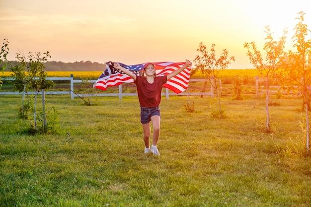 석양에 손에 미국 국기를 불고 들판에서 뛰는 평온한 아이