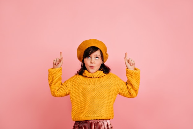 Carefree child in yellow beret looking up. caucasian kid making funny faces on pink wall.