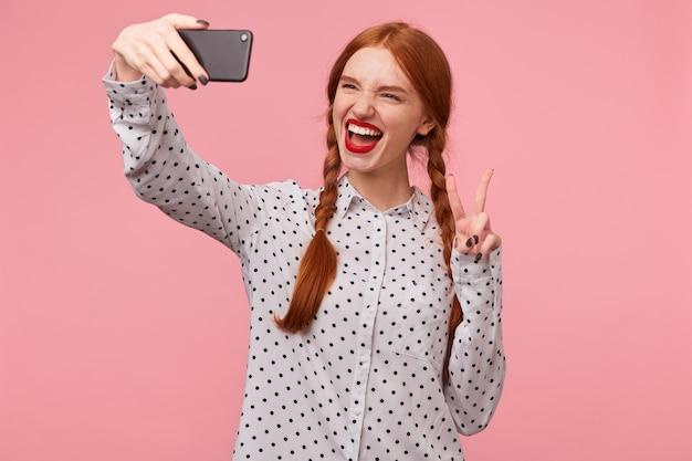 Беззаботная, уверенная, игривая, веселая, рыжая приветливо улыбается, показывая пальцами знак мира или победы, делает селфи на телефоне, носит белую рубашку в горошек изолированно