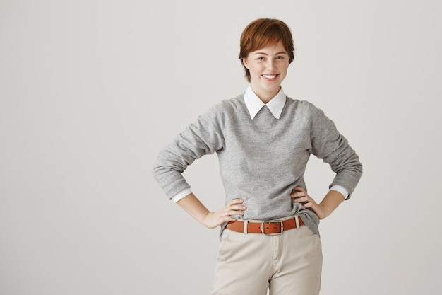 Carefree confident redhead girl with short haircut posing against the white wall