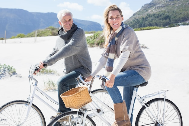 Carefree couple going on a bike ride on the beach smiling at camera