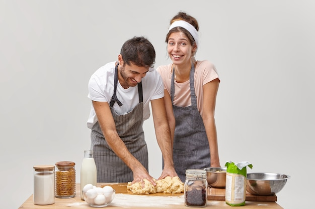 Carefree couple have fun at kitchen, knead dough for baking bread, busy preparing something delicious, wear aprons, surrounded with necessary products, isolated on white wall, try new family recipe