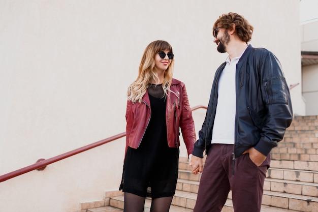 Беззаботная влюбленная пара гуляет по городу в городском стиле. выразительная блондинка с ее красивым парнем весело. весенний стильный наряд.