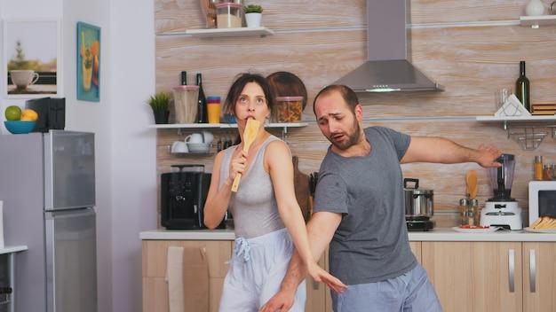 のんきなカップルが朝の朝食時に歌っています。 。陽気な妻と夫が笑って楽しんで面白い人生を楽しんでいる本物の既婚者ポジティブ幸せな関係