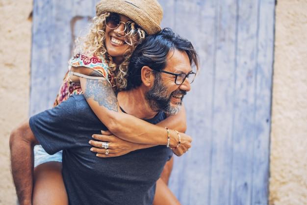 屋外で一緒に余暇を過ごすのんきなカップル、サングラスと麦わら帽子で陽気な入れ墨の女性にピギーバックの乗車を与える男。夫の背中でおんぶを楽しむ女性