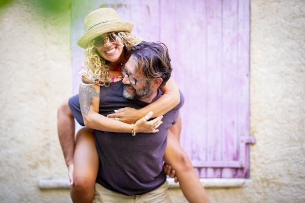 屋外で一緒に余暇を過ごすのんきなカップル、サングラスと麦わら帽子で陽気な入れ墨の女性にピギーバックの乗車を与える男