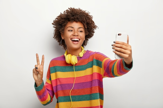 Carefree curly haired young woman takes selfie portrait on mobile phone, shows peace gesture, wears striped colorful jumper