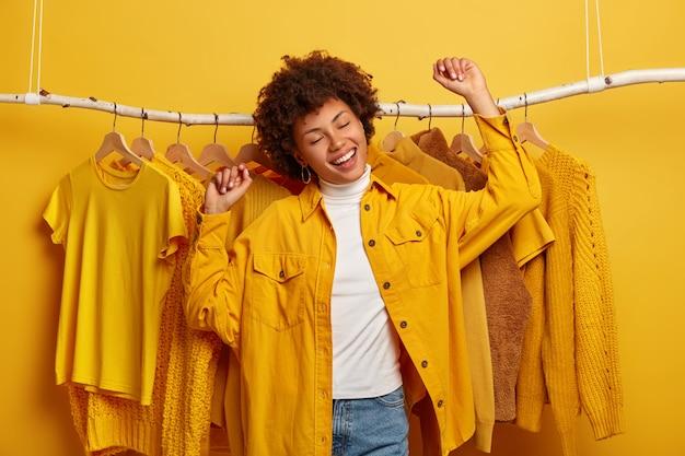 L'acquirente di abiti da donna riccia spensierata balla con felicità, alza le braccia, compra vestiti gialli della nuova collezione, si rallegra di una giornata di shopping di successo, è di buon umore, balla contro abiti sullo scaffale