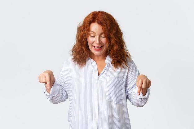 흥분하고 손가락을 아래로 가리키는 평온한 귀여운 중년 빨간 머리 여자는 훌륭한 프로모션 제안을 발견하고 광고와 함께 배너를 표시하고 흰 벽 위에 즐겁게 웃고 있습니다.