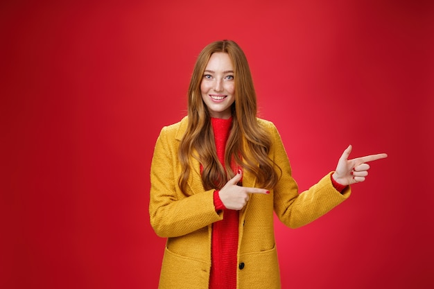 Carefree cute and tender young redhead female student in stylish yellow coat over dress pointing rig...