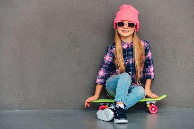 スケートボードでのんきなかわい子ちゃん。灰色の背景にスケートボードに座っている間笑顔でカメラを見ているサングラスの陽気な少女の全長