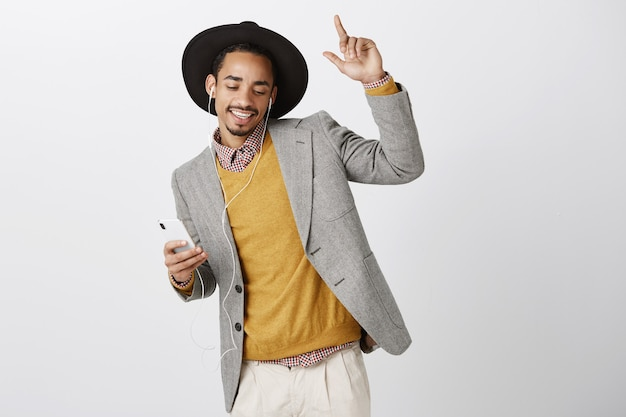 Carefree dancing african-american man listening music in headphones, smiling and holding smartphone