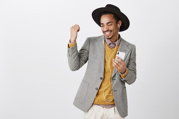 Musica d'ascolto dell'uomo afroamericano danzante spensierato in cuffie, sorridente e che tiene smartphone