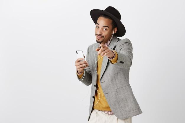 Беззаботный танцующий афро-американский мужчина слушает музыку в наушниках, улыбается и держит смартфон, указывая пальцем