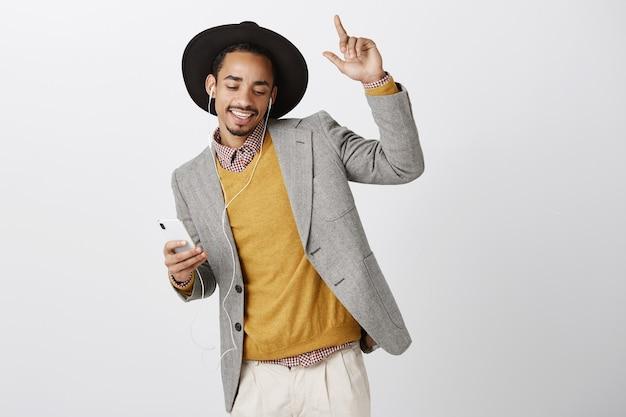 屈託のないダンスアフリカ系アメリカ人男性がヘッドフォンで音楽を聴く、笑顔でスマートフォンを保持