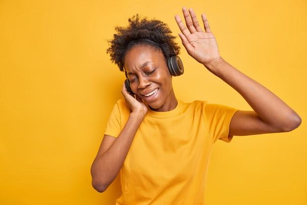 Carefree dark skinned millennial woman has fun moves with rhythm of music keeps arm raised