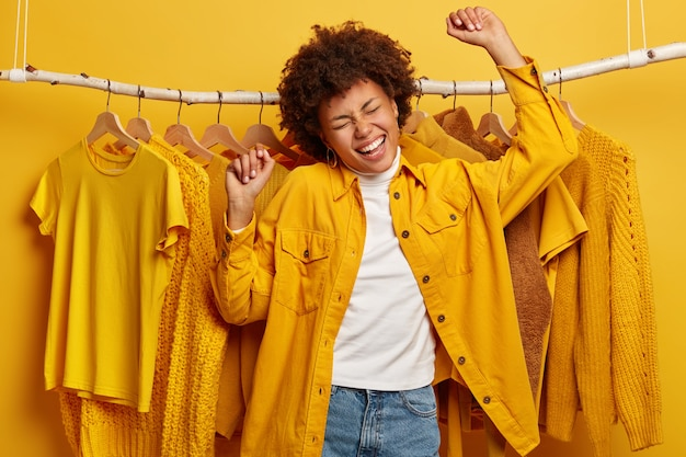 Carefree dark skinned woman dances in rhythm of music, makes victory movement, dressed in yellow shirt and jeans, moves against rack filled of fashionable clothes