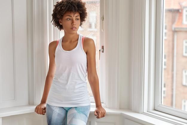 カジュアルなベストを着たのんきな浅黒い肌の女性は、バルコニーの窓の近くに立ち、脇に集中し、何かを考え、家庭的な雰囲気を楽しみ、家で一人で暇な時間を過ごします。居心地のよさのコンセプト