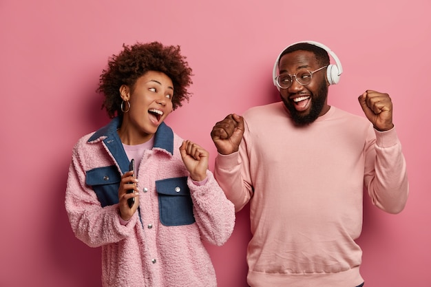 Carefree dark skinned woman and man bloggers have fun, hold mobile phone and listen audio track in headset, look positively at each other, pose against pink pastel wall. people and fun concept