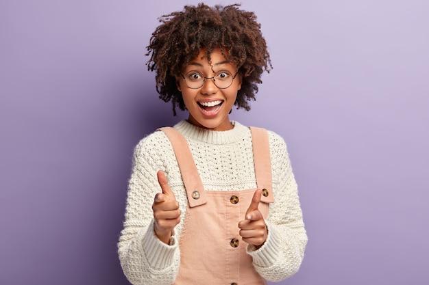 Беззаботная смуглая молодая женщина указывает прямо, размахивает пальцами, выглядит счастливо, выражает хорошие эмоции, носит повседневную одежду, изолирована от фиолетовой стены. пиф-паф