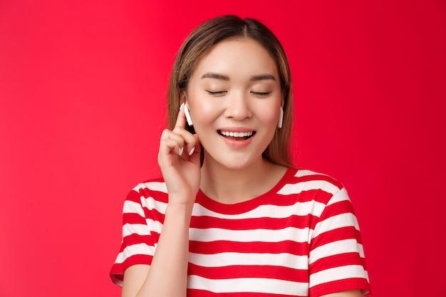 のんきな喜びのアジアの優しい女性は、ワイヤレスイヤホンを広く着用して笑顔で目を閉じて満足しています...