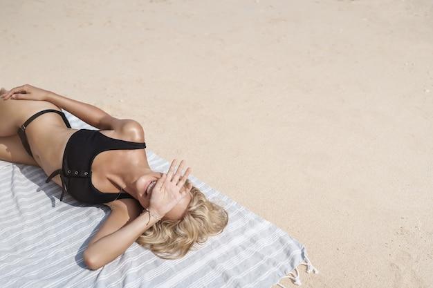 のんきな喜びの日焼けした金髪の若い女性は砂浜に横たわっています。