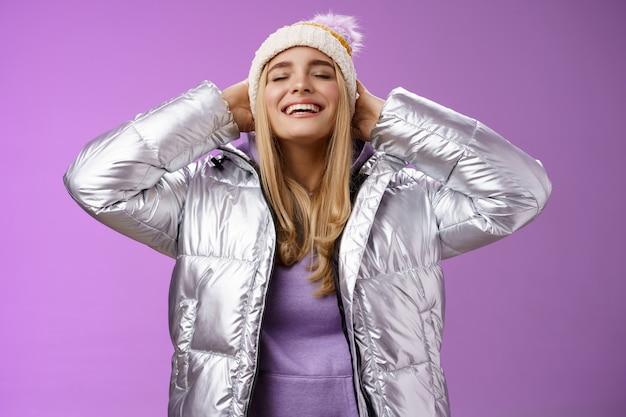 행복하게 호흡하는 신선한 공기 겨울 숲을 즐기는 평온한 기쁘게 젊은 매력적인 금발 여자