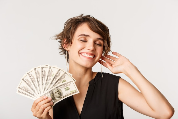 Carefree elegant rich woman smiling, showing money, standing over white.