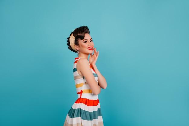 明るいドレスでポーズをとるのんきなエレガントな女性。青い背景で笑っているスタイリッシュなピンナップガールのスタジオショット。