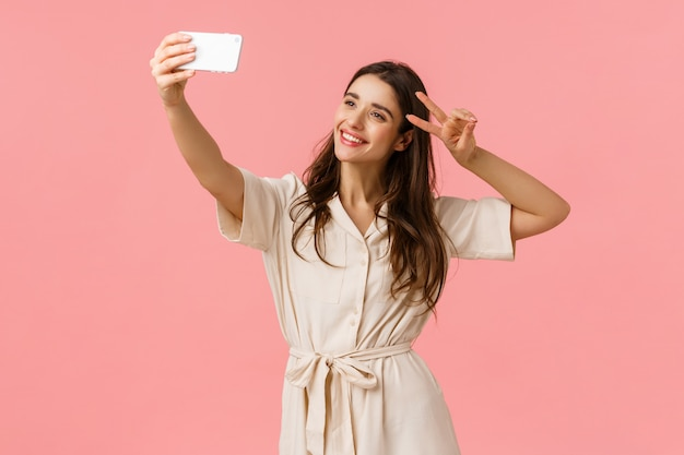 Carefree emotive, happy smiling brunette female in dress, holding phone, taking selfie and make peace sign, tilt head and smiling, sending positive vibes to followers, standing pink wall