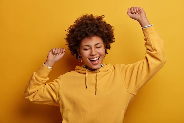 Giovane donna spensierata energica dalla pelle scura balla con le mani alzate, canta la canzone preferita, trionfa sulla vittoria, chiude gli occhi, esprime felicità, ottiene la vittoria o l'approvazione, indossa una felpa gialla