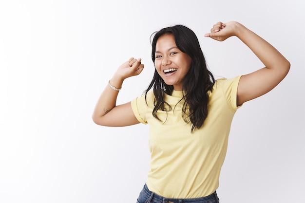노란색 티셔츠를 입은 평온한 에너지와 낙천적인 젊은 말레이시아 여성이 즐겁게 웃고 춤추며 카메라 춤과 행복하게 점프하는 모습