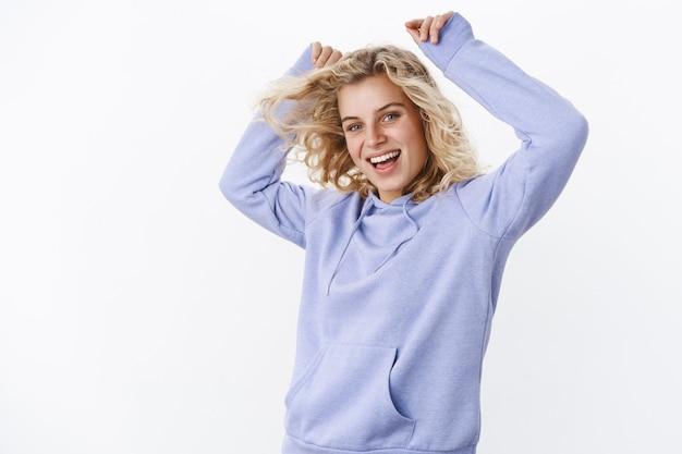 Spensierata giovane donna di 20 anni energizzata e carismatica con i capelli biondi e gli occhi azzurri che si diverte a passare il tempo in modo giocoso e rilassato ballando con le mani alzate e sorridendo ampiamente alla telecamera sul muro bianco